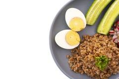 荞麦用鸡蛋和黄瓜在板材 免版税库存照片