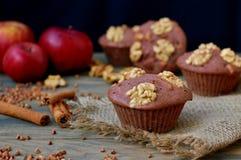 从荞麦的面筋免费松饼撒粉于,苹果、桂香和核桃在红色布料在棕色木桌上有黑背景 图库摄影