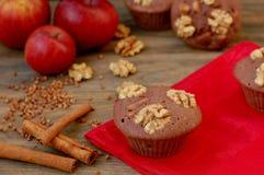 从荞麦的面筋免费松饼撒粉于,苹果、桂香和核桃在红色布料在棕色木桌上有黑背景 免版税库存照片
