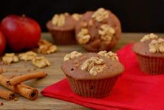 从荞麦的面筋免费松饼撒粉于,苹果、桂香和核桃在红色布料在棕色木桌上有黑背景 库存图片