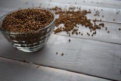 荞麦粥在碗和在木板 免版税库存图片