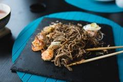 荞麦面条用金枪鱼虾和削片用在黑色的盘子的调味汁 亚洲食物背景 吃概念 餐馆p 免版税图库摄影