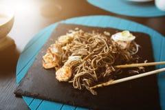 荞麦面条用金枪鱼虾和削片用在黑色的盘子的调味汁 亚洲食物背景 吃概念 餐馆p 免版税库存图片