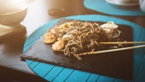 荞麦面条用金枪鱼虾和削片用在黑色的盘子的调味汁 亚洲食物背景 吃概念 免版税库存图片