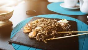 荞麦面条用金枪鱼虾和削片用在黑色的盘子的调味汁 亚洲食物背景 吃概念 库存照片