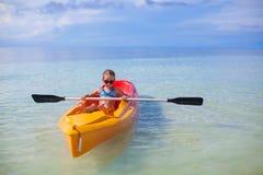 荡桨一条小船的小逗人喜爱的女孩在蓝色清楚的海 免版税库存图片