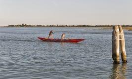 荡桨一艘长平底船的两位运动员在威尼斯盐水湖,意大利 免版税图库摄影