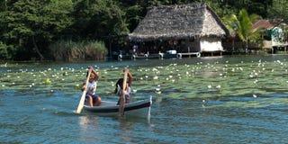 荡桨在一条小船的孩子。 库存图片