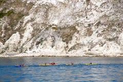 荡桨在侏罗纪海岸白垩峭壁旁边的划独木舟的人 库存照片