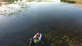 荡桨在夏天湖的一条可膨胀的小船的年轻行家朋友 慢动作空中的HD 影视素材