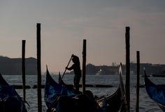 荡桨在大运河的平底船的船夫的剪影一艘长平底船在威尼斯,有圣乔治海岛的在背景中 免版税库存图片