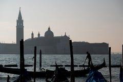荡桨在大运河的平底船的船夫的剪影一艘长平底船在威尼斯,有圣乔治海岛的在背景中 免版税图库摄影