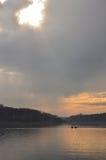 荡桨在有日落的美丽的湖 免版税库存照片