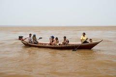 荡桨在棕色水表面上的小船的人们 免版税库存图片