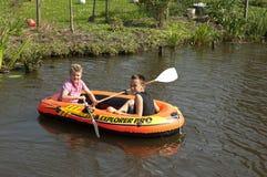 荡桨在橡胶充气救生艇,荷兰的孩子 图库摄影