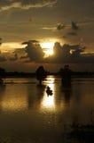 荡桨在河明亮的途中的人们  库存图片