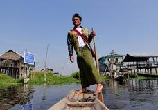荡桨在湖的一个缅甸人木小船在Inle,缅甸 库存照片