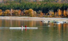 荡桨在湖的两个人一条小船 免版税库存图片