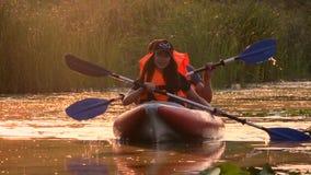 荡桨在独木舟的游人桨在沿河的晚上 慢的行动 股票录像