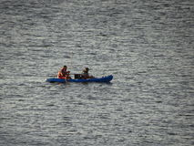 荡桨在皮船的两个人 库存照片