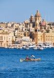 荡桨在盛大港口水的小船的两个男孩有t的 库存图片