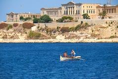 荡桨在盛大港口水的小船的两个男孩有t的 免版税库存图片