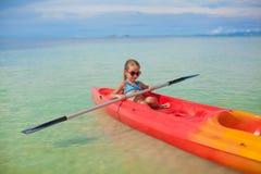 荡桨在蓝色清楚的小可爱的女孩一条小船 免版税图库摄影