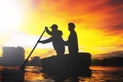 荡桨在被编织的竹篮子小船的两个人剪影  免版税库存照片