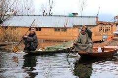 荡桨在Dal湖,斯利那加,克什米尔的两个地方人shikaras 免版税库存图片