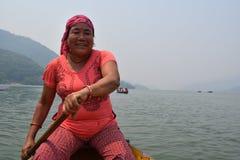 荡桨在Phewa湖的微笑的尼泊尔夫人一条小船 免版税库存照片