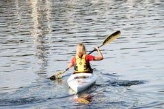 荡桨她的白色皮船的妇女 免版税库存图片