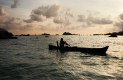 荡桨有他的桨的一个人剪影一条小船在海洋在日落,勿里洞岛 库存照片