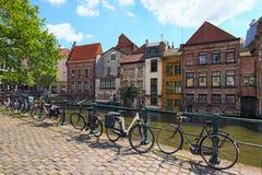 荡桨沿Lys河荷兰语的中世纪色的大厦:利斯河 与停放的自行车的堤防沿篱芭 免版税图库摄影