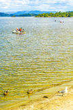 荡桨独木舟的人们用浆划在镇静蓝色Loch Lomond湖在苏格兰, 2016年7月21日, 库存图片