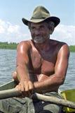 荡桨他的小船的资深渔夫画象 免版税图库摄影