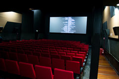 荧屏和红色椅子在戏院里面 免版税库存图片
