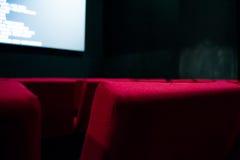 荧屏和红色椅子在戏院里面 免版税库存照片
