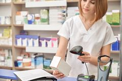药剂师与设备的扫描条形码在药房 免版税库存图片