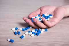 药剂过量概念-有药片的手在地板上 免版税库存图片