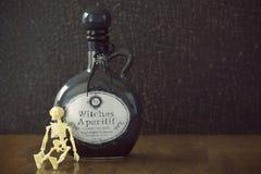 药商瓶子与头骨的巫婆酿造 库存图片
