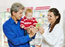 药房化学家、父亲和婴孩在药房 库存图片