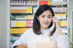 药房工作者谈话由电话,书桌的可爱的年轻微笑的女性有对耳朵的电话的 库存照片