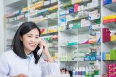 药房工作者谈话由电话,书桌的可爱的年轻微笑的女性有对耳朵的电话的 免版税库存照片