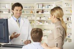 药房的药剂师与母亲和孩子 免版税库存照片