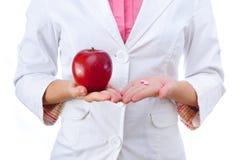 药房 药片或苹果,维生素的两个来源 库存照片