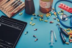 药片、医疗数字式片剂、胶囊和一个听诊器在医生` s书桌上 药房医学概念 免版税库存照片