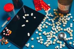 药片、数字式片剂、胶囊和一个听诊器在医生Table 药房医学概念 免版税库存图片