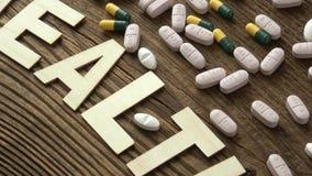 药片以在棕色木背景的题字健康 股票录像