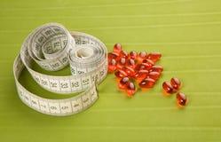 药片和卷尺在绿色背景 免版税库存照片