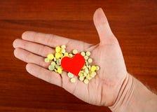 药片和心脏形状在手上 免版税图库摄影